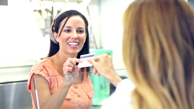 vidéos et rushes de travailleur dans la salle à manger en tenant le paiement par carte de crédit du client - relation client