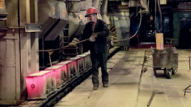 Worker in foundry controlling iron smelting in furnaces video