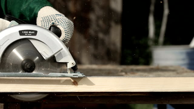 vídeos y material grabado en eventos de stock de trabajador en guantes de corte un tablón de madera con la sierra circular de mano - tablón
