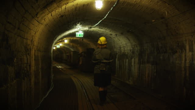 stockvideo's en b-roll-footage met werknemer in hard hat is walking in mining tunnel - riool