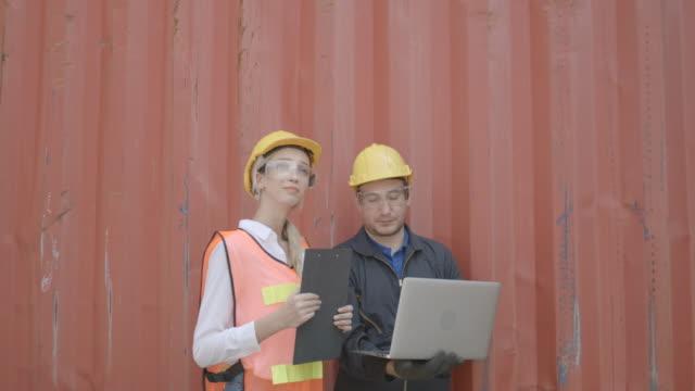 vidéos et rushes de travailleur dans l'équipe logistique, homme et femme travaillant avec l'ordinateur portable vérifiant le contrôle de chargement des marchandises conteneur de cargaison pour se préparer au transport dans le port industriel à la grande expédition c - bloc note