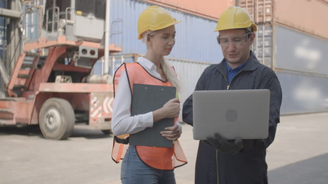 worker in logistic, man and woman working team with laptop checking control loading goods cargo container to prepare for transport in industrial harbour at large commercial shipping for import export. - rozładowywać filmów i materiałów b-roll