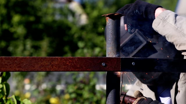 Worker in protective mask welding steel railings outdoors video