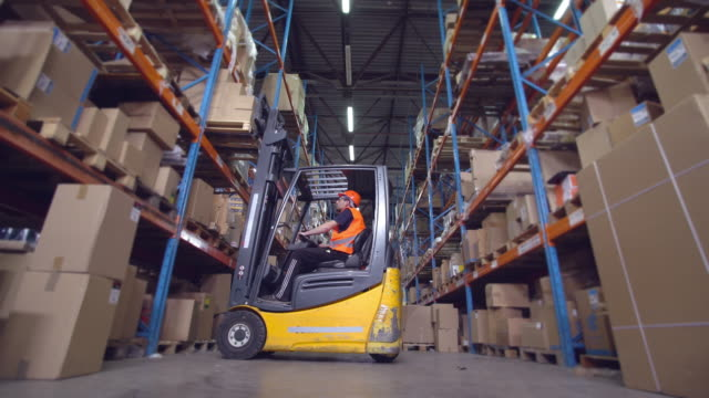 worker in storehouse driving on the special vehicle. forklift operator puts boxes with goods on the metal racks forklift stock videos & royalty-free footage