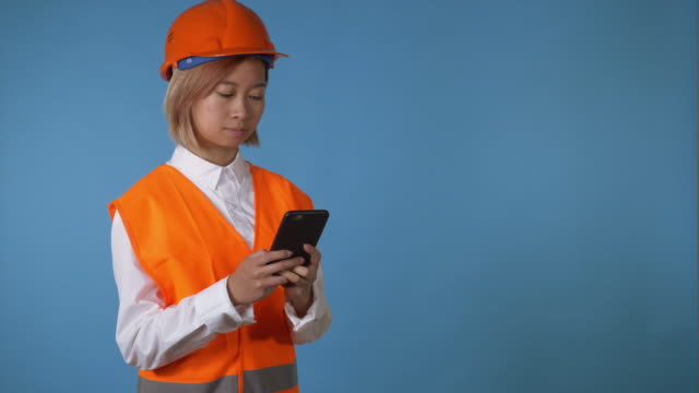 worker in uniform texting on smartphone portrait young asian female posing wearing orange hard hat vest using mobile messaging or surfing internet touch screen on blue background in studio. attractive korean woman with blond hair wearing white casual shirt looking at the camera smiling padding stock videos & royalty-free footage