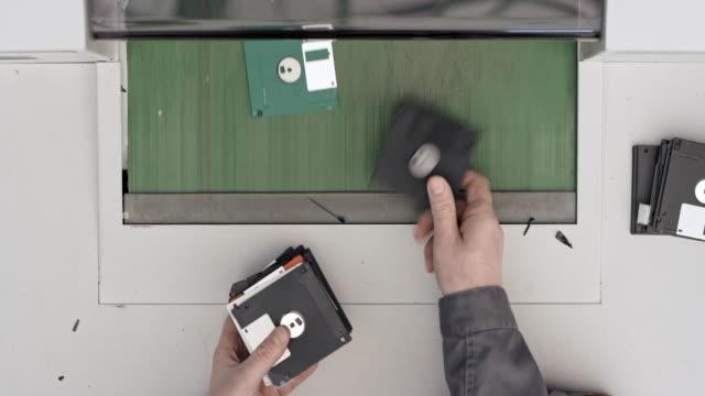 vídeos y material grabado en eventos de stock de trabajador de ld insertar disquetes y discos compactos en la trituradora - disquete