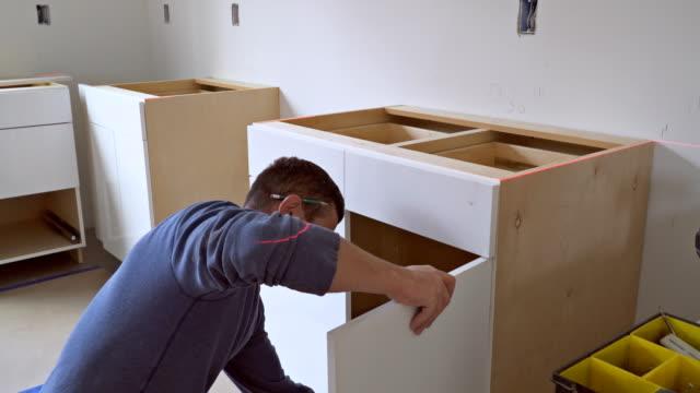 vídeos de stock e filmes b-roll de worker installing kitchen cupboard installation of kitchen. worker installs kitchen cabinet. - obras em casa janelas