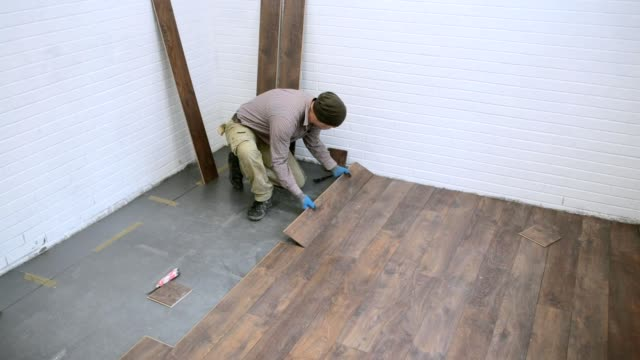 Worker installs brown laminate in the room.