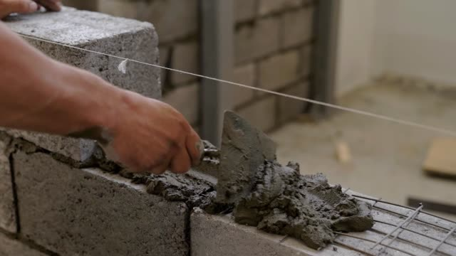 worker is applying cement mortar on a wall for lying building blocks, distributing evenly, using spatula video