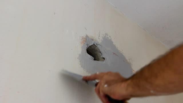 worker is applying skim coating material around wall socket before painting - dziura filmów i materiałów b-roll