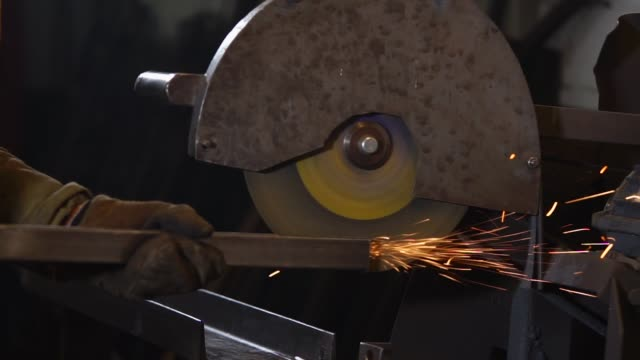 Worker is grinding edge of metal beam by disk of polishing machine in factory Metalworker is abrading rib of iron girder. He is holding it near rotating big disk of industrial buffing machine grinder industrial equipment stock videos & royalty-free footage