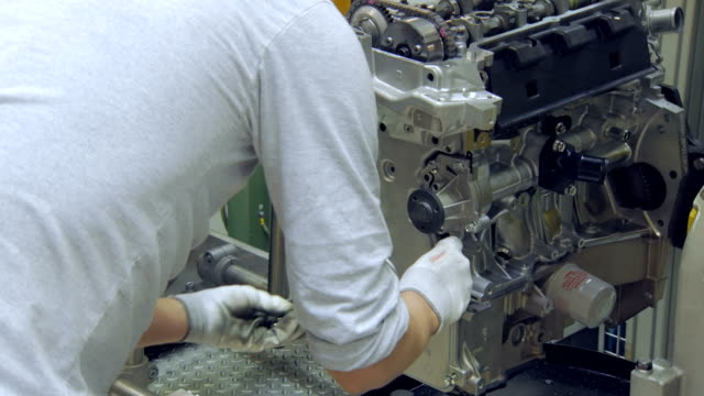worker is putting bolts into car engine, modern car production, workshop