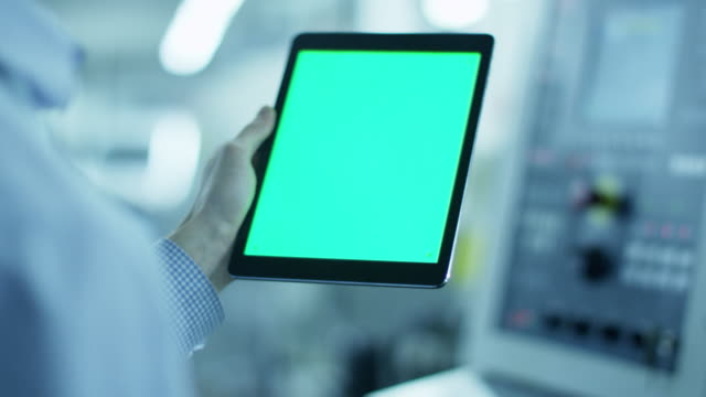 Worker is Using Tablet PC with Green Screen in Portrait Mode video