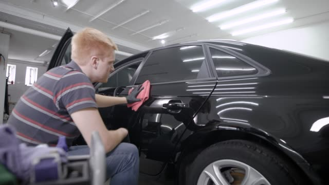 worker is wiping doors of luxury black car after protective processing and washing in a garage, sitting near - close up auto video stock e b–roll