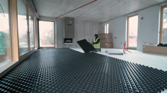 ds worker om svarta isoleringspaneler för golvvärme - construction workwear floor bildbanksvideor och videomaterial från bakom kulisserna