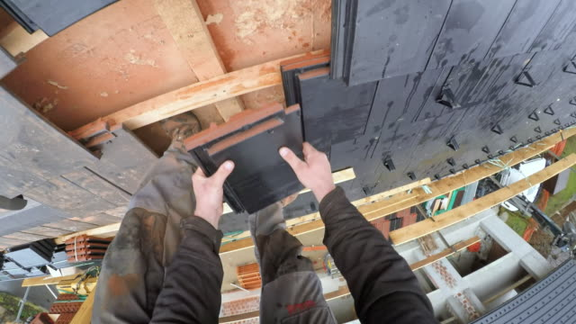 POV Worker laying roof tiles