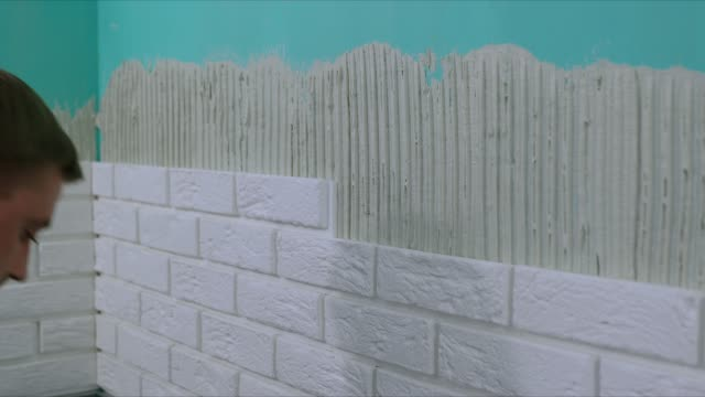 worker laying white brick tiles on the wall - piastrella video stock e b–roll