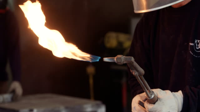 Worker lighting up a tourch in a metal workshop video