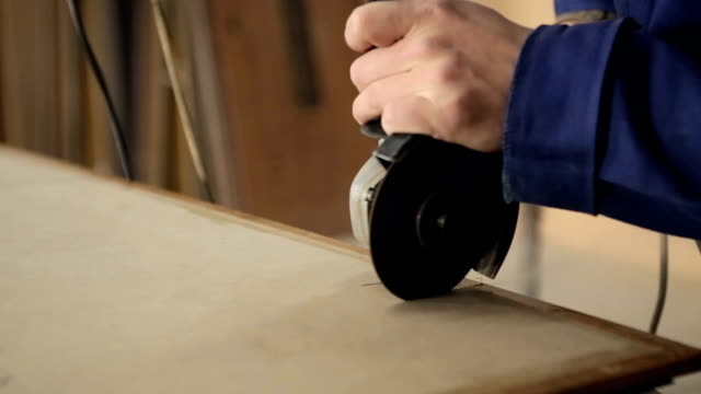 Worker makes cuts on a wooden workpiece.