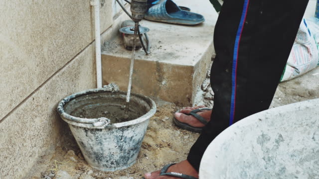 Worker making cement mix with water for building construction
