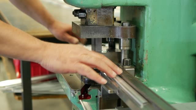 worker making holes in metal plates with a punching drilling machine - colpire con un pugno video stock e b–roll