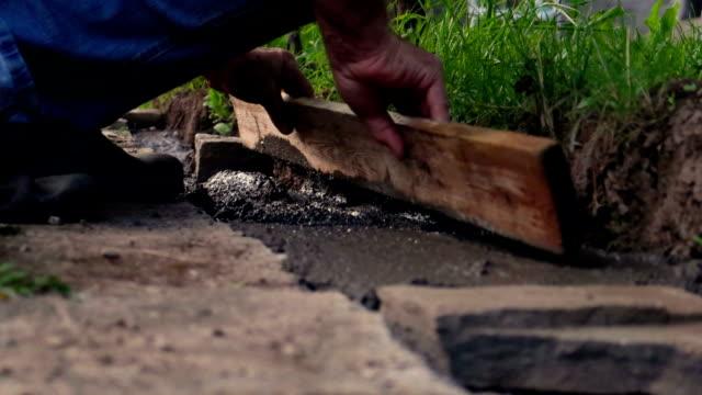 A worker / man build a stonewall make a masonry