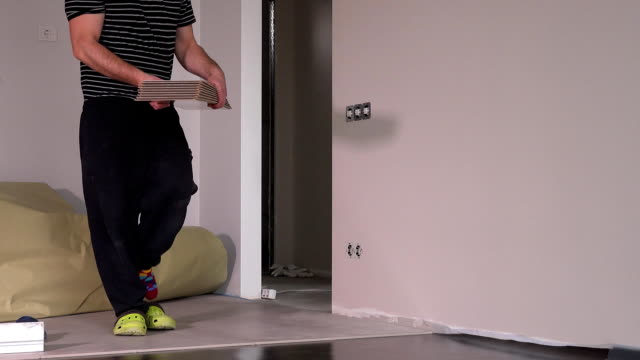 Worker man carry laminate floor boards in new apartment video