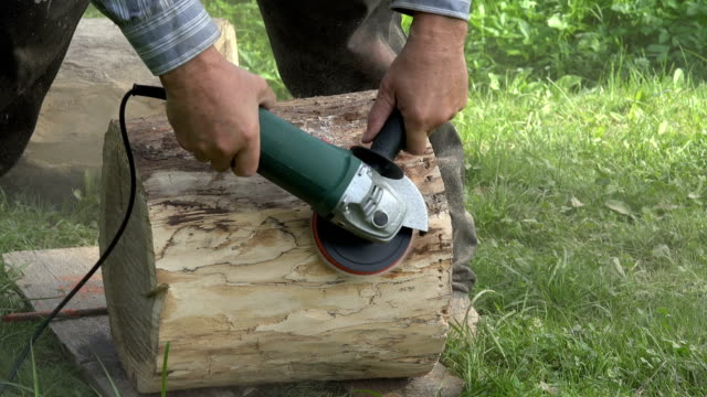 worker man hand with electric sander tool sand tree log. dust rising in air. closeup. 4k - levigatrice video stock e b–roll