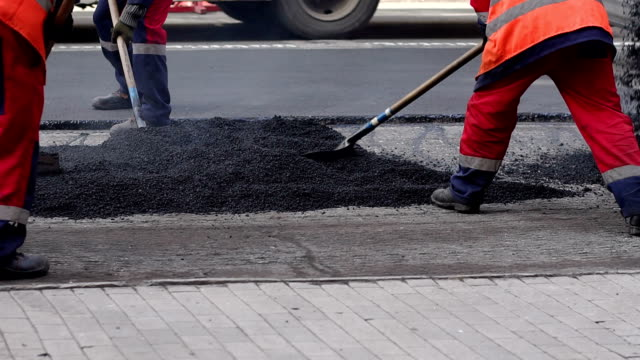 Worker man lays asphalt on a road repair road paving. Repair of roads. Asphalt.