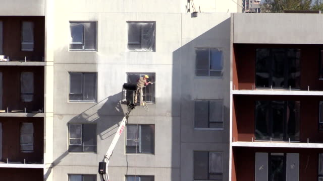 Worker man spray thermal paint on flat apartment house wall