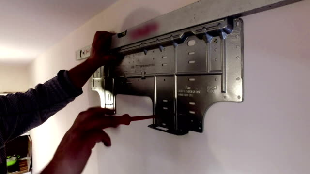 Worker manually tightening a screw with screwdriver on wall mounted air conditioner metal holder video