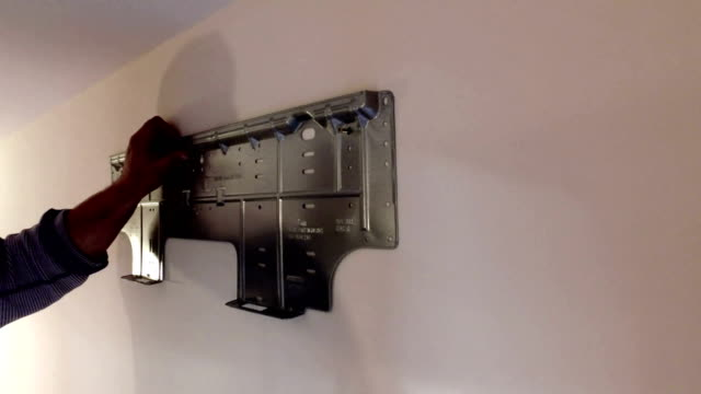 Worker manually tightening an artwork hang screw into a drilled hole in white wall with screwdriver, renovating, decorating and improving home. Do-it-yourself (DIY) concept video