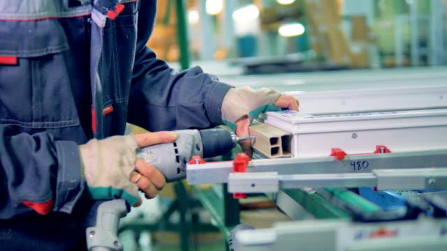 vídeos de stock e filmes b-roll de worker manufacturing plastic window. assembly line of pvc windows and doors. - bit código binário