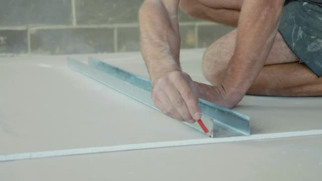 Worker marking a drywall sheet for installing it in newly built house. video
