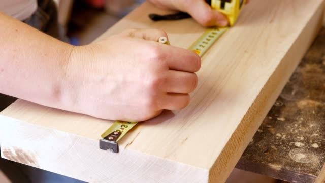 Worker measures the tape measure and pencil distance on the wood Board. Joinery. Hands close-up. Worker measures the tape measure and pencil distance on the Board. Joinery instrument of measurement stock videos & royalty-free footage