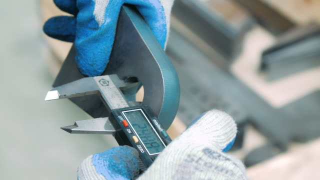 Worker measuring inner diameter of iron part with electronic caliper Worker measuring inner diameter of iron part with electronic caliper. Male hands with caliper gauge measuring size of detail of machine metal part. Metal vernier caliper with indicator panel quality control stock videos & royalty-free footage