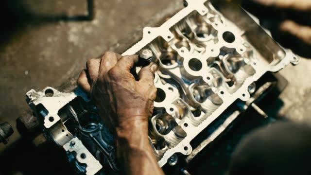 arbeiter mechanic vorbereitung und bohrung kernpistole oder plunger für die befestigung von ventilkopfmaschinen in der werkstatt. - steckschlüssel stock-videos und b-roll-filmmaterial