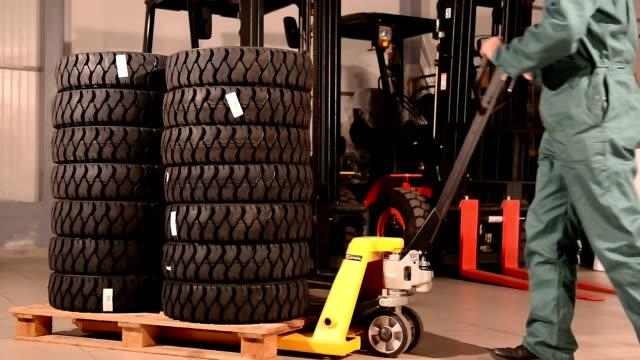 operaio camion pneumatici muoversi pallet carrello elevatore a forca - truck tire video stock e b–roll