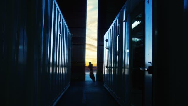 stockvideo's en b-roll-footage met werknemer opent de deur van een container magazijn in de schemering. - warehouse worker