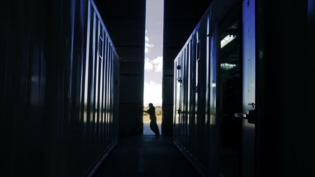 Worker Opens Door Of A Container Warehouse in the Morning.