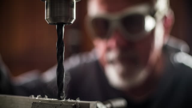 Worker operating a bench drilling machine video