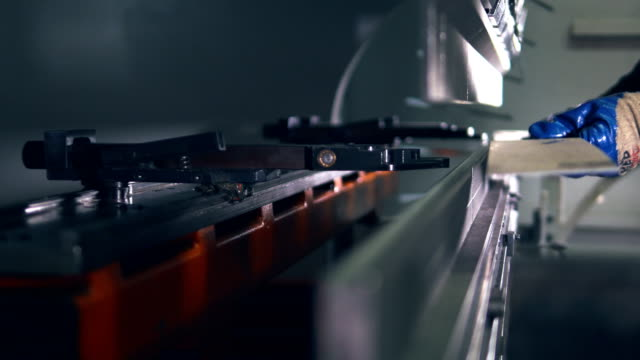 worker operating cnc hydraulic press brake. bending sheet of metal. close-up. - inarcare la schiena video stock e b–roll