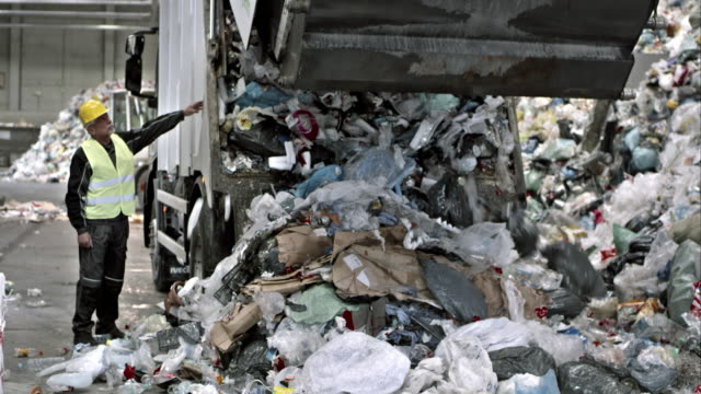Worker operating the garbage truck in the recycling facility video