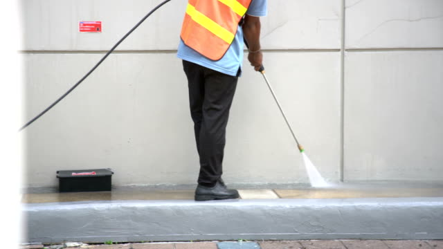 worker or cleaning staff is using a high-pressure water spray - marciapiede video stock e b–roll