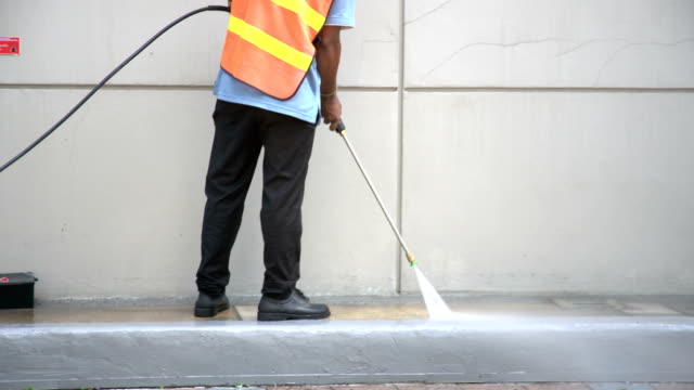 worker or cleaning staff is using a high-pressure water spray - alto video stock e b–roll
