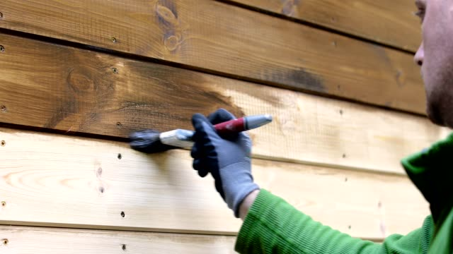worker painting house exterior with brown wood protective color worker painting house exterior with brown wood protective color timber stock videos & royalty-free footage