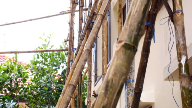 Worker Painting House While Standing On Bamboo Scaffold video