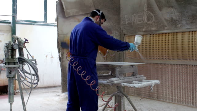 worker painting in a factory - industrial painting with spray gun - dolly video