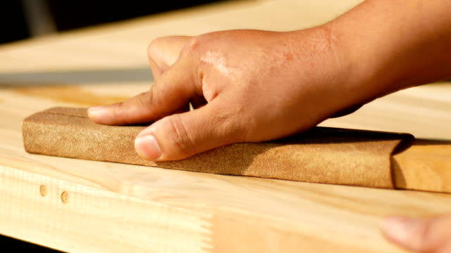 worker polishing wood table with sand paper with nature sunlight - carta vetrata video stock e b–roll