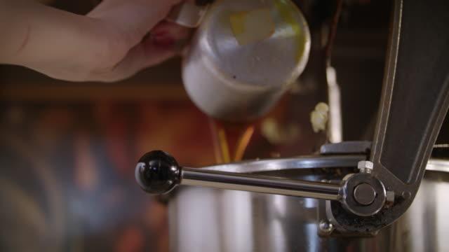vídeos de stock, filmes e b-roll de trabalhador jogando óleo na pipoqueira. preparando-se para a produção de pipoca - balde pipoca
